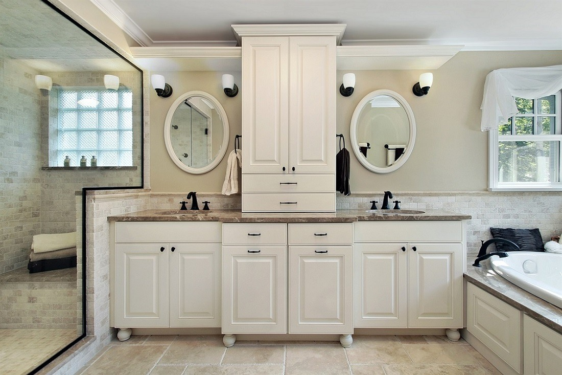 Double vanity bathroom with wall sconce lights above each mirror.