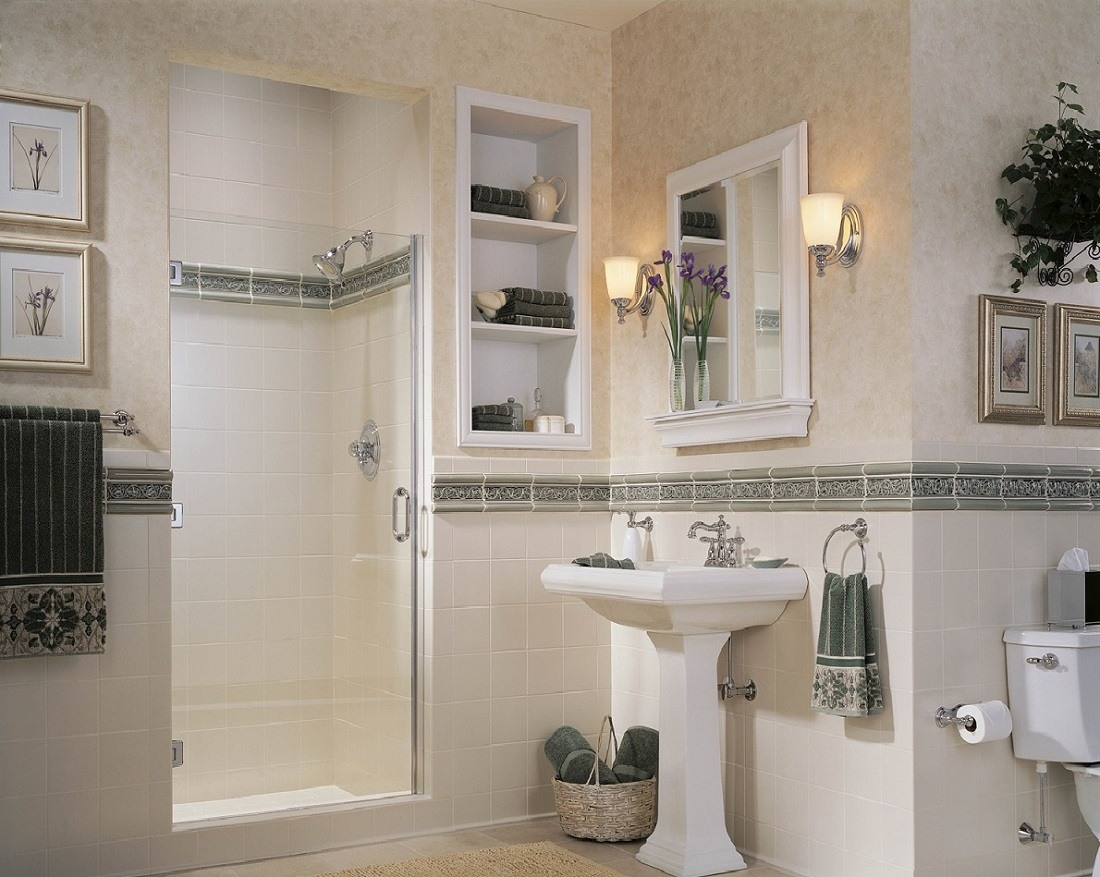 Small sink with two wall sconces above on either side of the mirror.