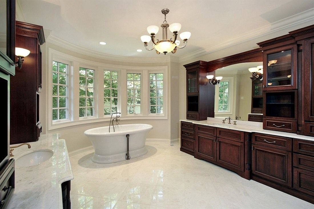 Large open bathroom with tub at far end in window nook with chandelier and recessed lighting in the ceiling and wall mounts along the mirrors.