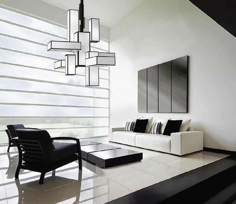 Geometric chandelier hanging over living room with view outside.