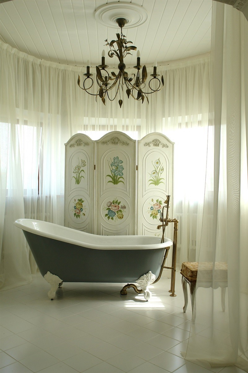 Decorative chandalier hanging over bathtub surrounded by white linen curtains.