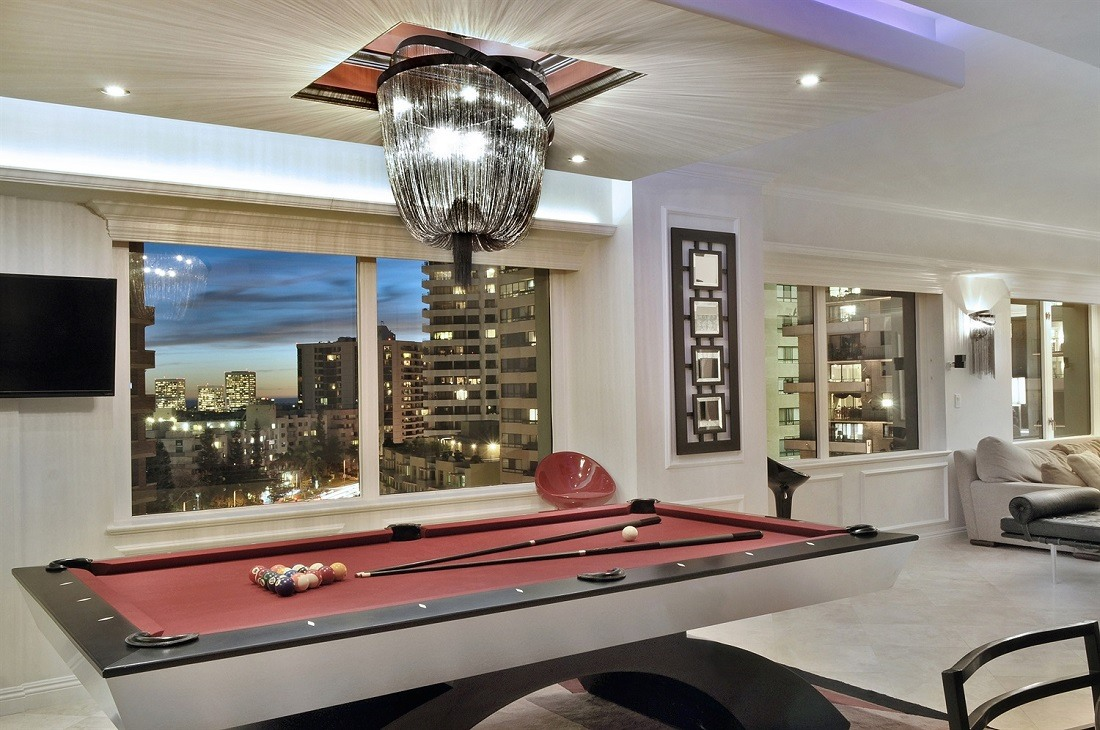 Fancy chandalier over billiard table with window view overlooking city.
