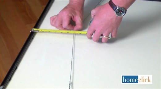 Man measuring distance between taught wire and picture frame edge