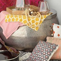 Close up image of boho style decor featuring a metal stool, pillows, and colorful fabric