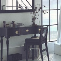 Black mirror, writing desk, and chair in a well-lit coastal room