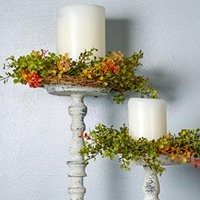 Rustic candle sticks with white candles and colorful wreaths