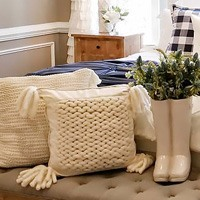 Image of farmhouse decor featuring knit pillows and a tufted school